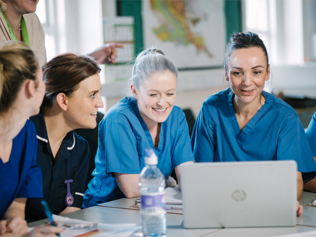 Student nurses using a laptop together.