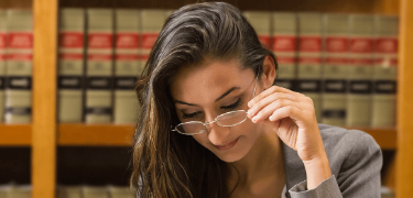 Woman with glasses in front of a bookshelf