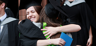 学生们 hugging at graduation ceremony