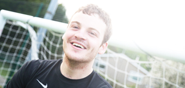 A boy smiling in front of a football goal