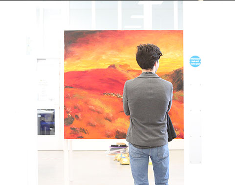 boy looking at paintings