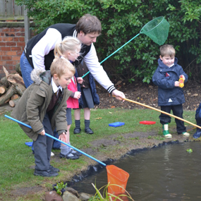 male with children fishing in a pond